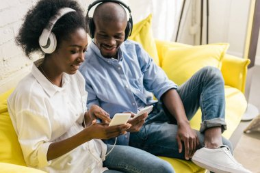 smiling african american listening music in headphones and using smartphones while resting on sofa at home