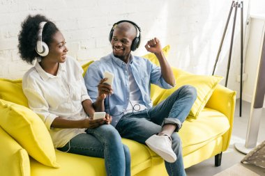 cheerful african american listening music in headphones with smartphones while resting on sofa at home