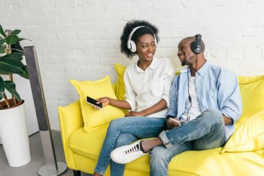 smiling african american listening music in headphones with smartphones while resting on sofa at home