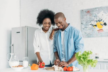 portrait of african american cooking breakfast together in kitchen at home