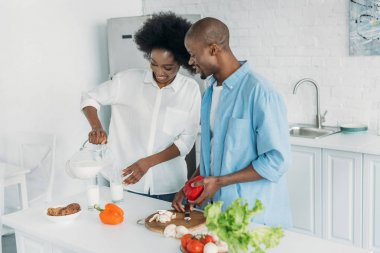 smiling african american woman pouring milk into glass while husband cooking breakfast in kitchen at home