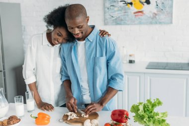 african american woman looking at husband cooking breakfast in kitchen at home