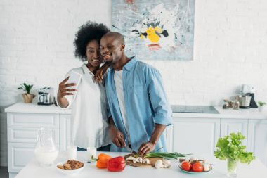 african american couple taking selfie together while cooking breakfast in kitchen at home