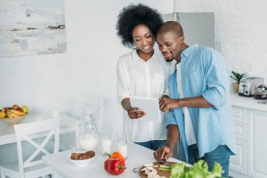 african american using tablet and fresh vegetables on table in kitchen at home