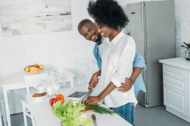 smiling african american cooking breakfast together in kitchen at home