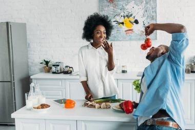 african american couple with fresh vegetables on table in morning at home
