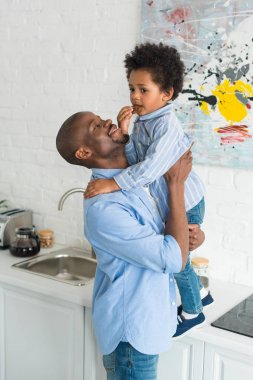african american man holding little son with cookie in kitchen at home