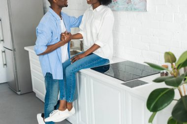 partial view of african american couple holding hands in kitchen at home