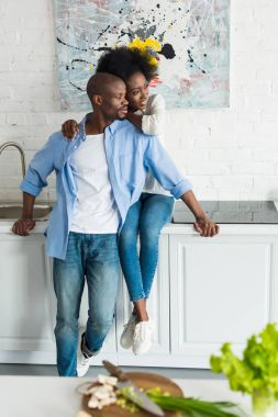 happy african american woman hugging husband in kitchen at home