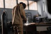 Rückansicht des Fertigungsarbeiters beim Schweißen von Metall mit Funken in der Fabrik