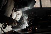 pracovník v ochranné masce svařování kovů v továrně