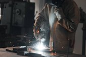 Photo cropped shot of worker in protection mask welding metal at factory