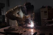 Photo  worker in protection mask welding metal at factory