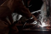 Fotografie cropped image of manufacture worker welding metal with sparks at factory