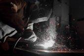 Fotografie boční pohled na pracovníka v ochranné masce svařování kovů v továrně