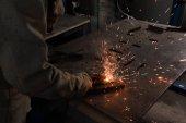 Fotografie Oříznout obrázek pracovníka v ochranné masce svařování kovů v továrně