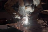 Fotografie čelní pohled svářečka v ochranné masce pracující s kovem v továrně