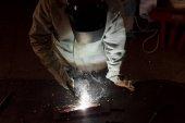 Fotografie pohled z vysokého úhlu pracovníka v ochranné masce svařování kovů v továrně