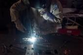 Oříznout obrázek svářečka v ochranné masce pracující s kovem v továrně