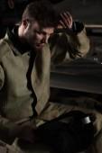 Fotografie unavený mladý muž dělník s ochrannou maskou v továrně