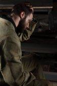 vista laterale di giovane operaio maschio stanco seduto alla fabbrica