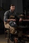 usměvavý dělník v uniformě v továrně drží ochranná maska