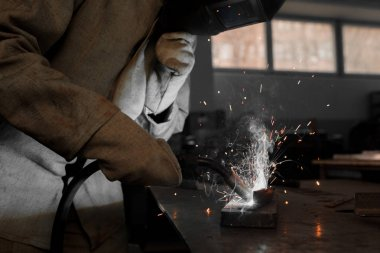 cropped image of manufacture worker welding metal with sparks at factory