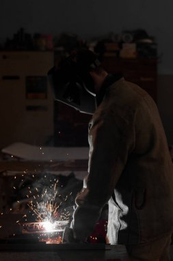 side view of manufacture worker welding metal with sparks at factory