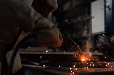 cropped shot of manufacture worker welding metal with sparks at factory