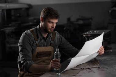 workman sitting with bottle of water and looking at blueprint