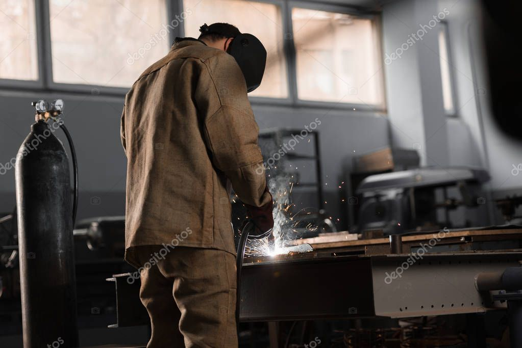 Rear view of manufacture worker welding metal with sparks at factory stock vector