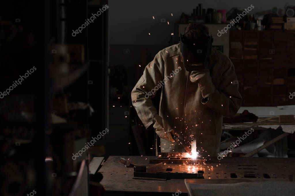 Worker in protection mask welding metal at factory stock vector