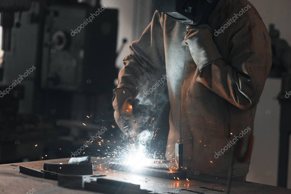 Cropped shot of worker in protection mask welding metal at factory stock vector
