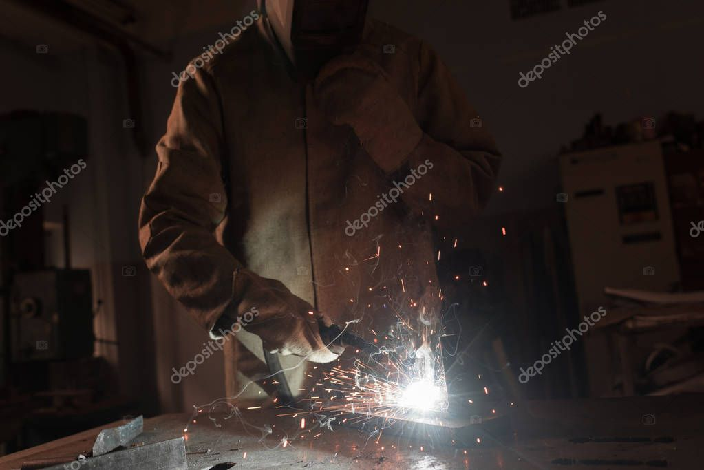 Cropped image of worker in protection mask welding metal at factory stock vector