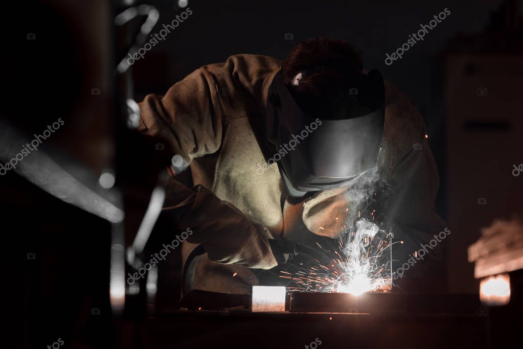 Front view of welder in protection mask working with metal at factory stock vector