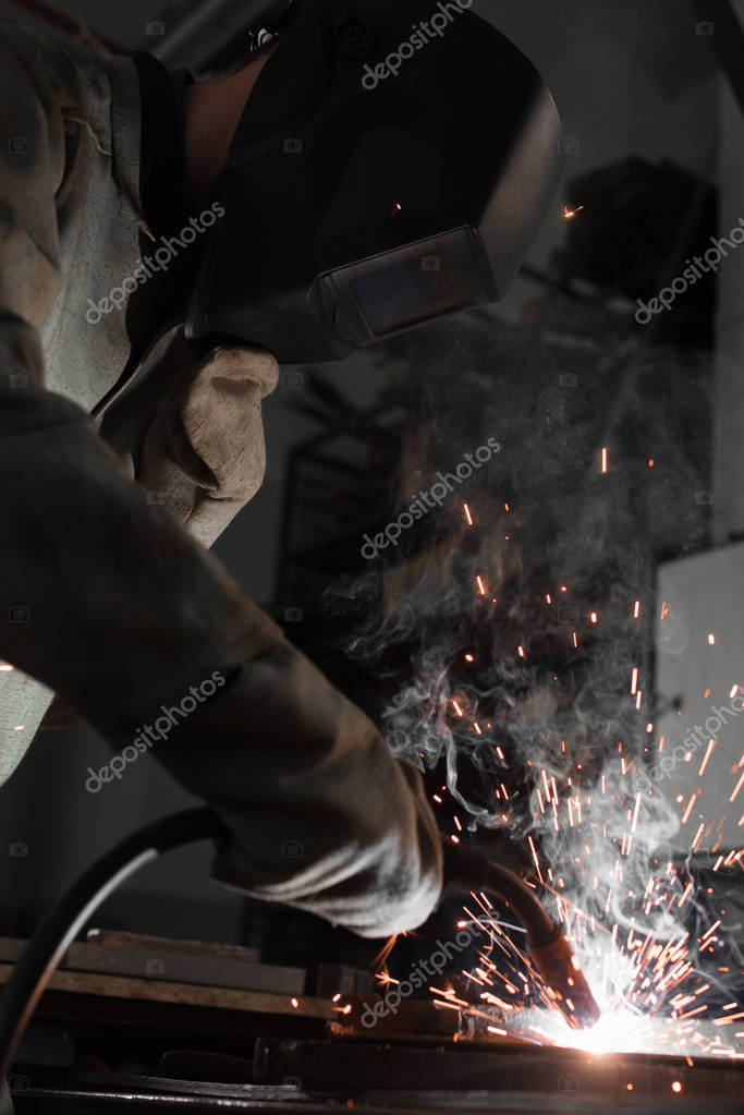 Manufacture worker welding metal with sparks at factory stock vector