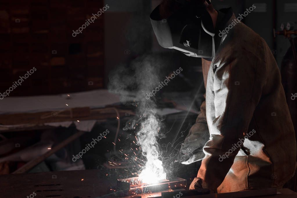 Welder in protection mask working with metal at factory stock vector