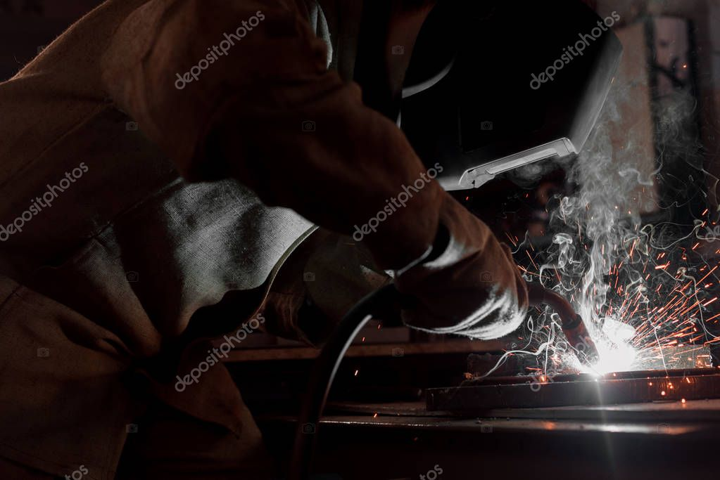 Cropped image of manufacture worker welding metal with sparks at factory stock vector