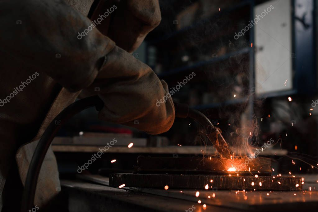 Cropped shot of manufacture worker welding metal with sparks at factory stock vector