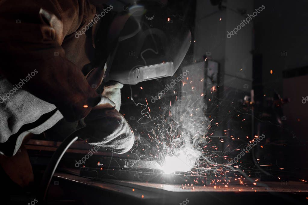 Side view of worker in protection mask welding metal at factory stock vector