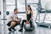 Mladá sportovkyně sedí na fitness míč a mluví s osobním trenérem s digitálním tabletu v tělocvičně