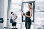 mladé samice trenéra s digitálním tabletu a atletický muž s činka v posilovně
