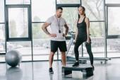 mužského osobního trenéra a mladé sportovkyně dělá step aerobik cvičení s činkami v posilovně