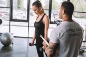 Mladá sportovkyně dělá krok aerobik cvičení s činkami a mužského osobního trenéra s schránky v tělocvičně