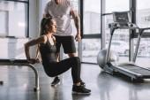 Fotografie männlichen Personaltrainer betrachten Sportlerin Plank im Fitnessstudio zu tun