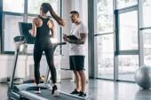 Fotografie männlichen Personaltrainer mit Timer während Sportlerin auf Laufband im Fitnessstudio