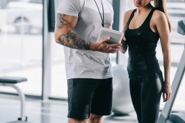 cropped image of male personal trainer showing schedule on digital tablet to sportswoman at gym