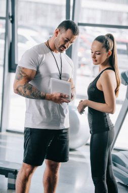 male personal trainer showing schedule on digital tablet to young sportswoman at gym
