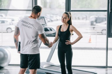 rear view of male personal trainer and young sportswoman shaking hands at gym