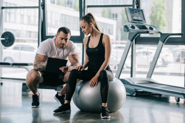 male trainer writing in clipboard and young sportswoman sitting on fitness ball at gym